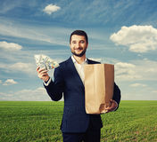 Man holding paper bag and money. Smiley businessman holding paper bag and money at outdoor Stock Photography