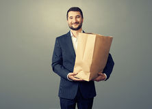 Man holding paper bag over dark Royalty Free Stock Image