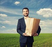 Man holding paper bag over green field. Handsome businessman holding paper bag and smiling over green field Royalty Free Stock Photography