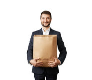 Man holding paper bag and smiling Royalty Free Stock Image