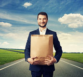 Man holding paper bag and smiling Stock Photography