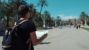 Male tourist is reading map of city walking on near Arc de Triomphe in Barcelona stock video footage