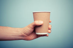 Man holding paper cup. A man is holding a brown paper cup Stock Image