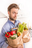 Man holding paper grocery shopping bags in the kitchen Royalty Free Stock Images
