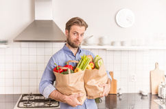 Man holding paper grocery shopping bags in the kitchen Royalty Free Stock Photos