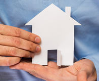 Man holding paper house in his hands Stock Photos