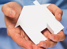 Man holding paper house in his hands Stock Image
