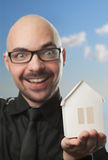 Man holding a paper house. Real estate concept on a blue background Royalty Free Stock Images