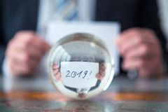 Man holding paper with the numbers 2019 in front of glass ball royalty free stock photography