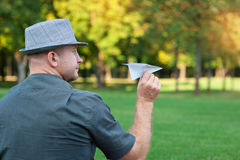 Man holding a paper plane in the hand on meadow.  Royalty Free Stock Photos