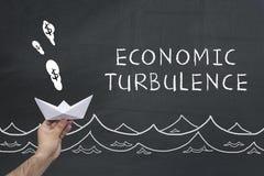 Economic turbulence concept on chalkboard. Man holding paper ship on blackboard with words: Economic turbulence Royalty Free Stock Image