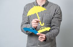 Man holding paper symbols. Man holding cardboard blue model of cars and yellow umbrella. Concept for vehicle insurance Stock Photography