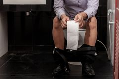 Man holding paper in toilet. Man sitting are holding paper in the toilet at office Stock Image