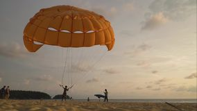 A man is holding a parachute downwind on the beach. Timelapse. stock video
