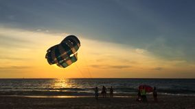 Man Holding a Parachute in the Wind on the Beach During Sunset. Karon beach, Phuket, Thailand. HD silhuette slowmotion. stock footage