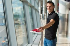 Man holding passports and boarding pass at airport Stock Photos