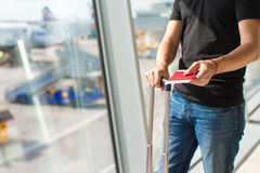 Man holding passports and boarding pass at airport Royalty Free Stock Image