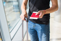 Man holding passports and boarding passport at Royalty Free Stock Photo