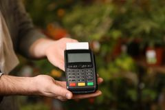 Man holding payment terminal in floral shop, closeup. Space for text stock photo
