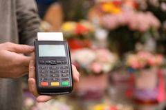 Man holding payment terminal in floral shop, closeup. Space for text stock photography