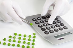 Man holding pea in tweezer while using calculator Royalty Free Stock Images