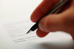 Man holding a pen while doing document. Closeup of a man holding a pen while doing document. Shot with shallow depth of field Royalty Free Stock Photos
