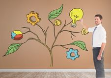 Man holding pen and Drawing of Business graphics on plant branches on wall Royalty Free Stock Images