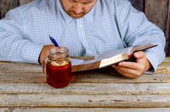 Man is holding a pen in his hand with an openHoly Bible as well as tea on the table royalty free stock photography