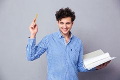 Man holding pencil and folder with files. Happy casual man holding pencil and folder with files over gray background. Looking at camera stock photo