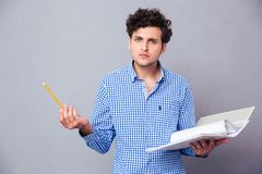 Man holding pencil and folder with files. Young serious man holding pencil and folder with files over gray background. Looking at camera stock images