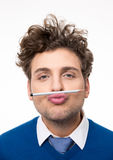 Man holding a pencil between the lips and nose Royalty Free Stock Photography
