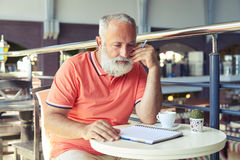 Man holding pencil and looking at empty notepad Stock Images