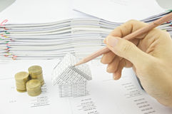 Man holding pencil over house on balance sheet Stock Photo