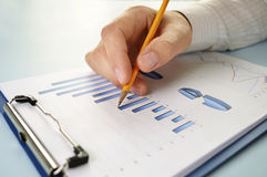 Man holding a pencil working on a graph Royalty Free Stock Images
