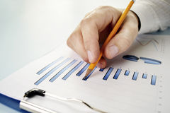 Man holding a pencil working on a graph Stock Photography