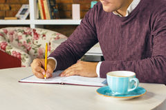 Man holding pencil and writing on a paper in the diary Stock Image