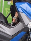 Thai Man filling petrol into a motercycle. Man holding petrol dispenser filling petrol into a blue motorcycle Stock Photos