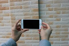 Man holding phone against a brick wall