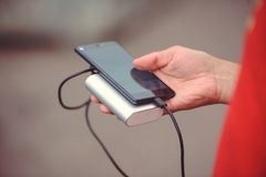 The man is holding the phone and the charger. Powerbank and smartphone in hand. Power-saving device power bank smartphone Stock Image