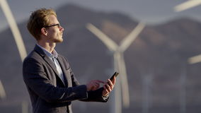 The man holding the phone. The close-up video of man holding the phone and looking at the same time to the side with operating windmills on the background stock video footage