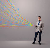 Man holding a phone with colorful abstract lines Royalty Free Stock Image