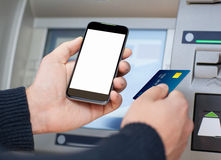 Man holding phone and a credit card at an ATM Royalty Free Stock Photography