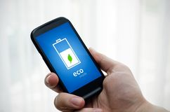 Man holding phone with eco battery mode Stock Photos