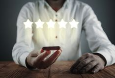 Man holding phone with five stars. Increase rating stock photo