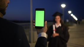 Man holding the phone with green screen like he is taking a picture of a graduate female student who is standing in stock footage
