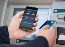Man holding phone online shopping and credit card at ATM Royalty Free Stock Photo