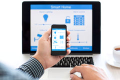Man holding phone with program smart home on the screen Royalty Free Stock Image