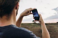 Man holding phone and taking photo of amazing sunset landscape v royalty free stock images