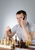 Man holding a phone in their hands and playing chess Stock Photo