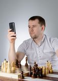 Man holding a phone in their hands and playing chess Royalty Free Stock Photography